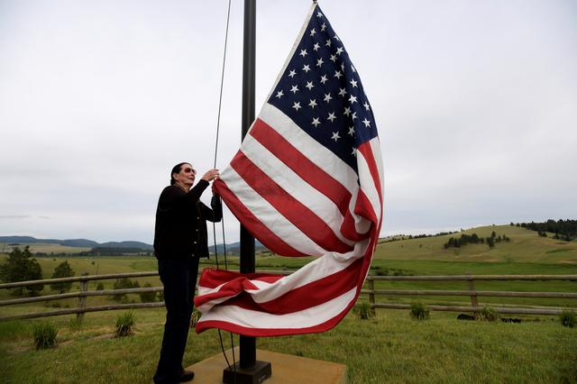 Cattle rancher Arlene Mackay, 80, raises the American flag at her ranch in Avon, Montana, U.S. June 28, 2019. Picture taken June 28, 2019. REUTERS/Tommy Martino