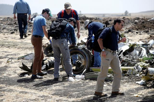 FILE PHOTO: American civil aviation and Boeing investigators search through the debris at the scene of the Ethiopian Airlines Flight ET 302 plane crash, near the town of Bishoftu, southeast of Addis Ababa, Ethiopia March 12, 2019. REUTERS/Baz Ratner/File Photo