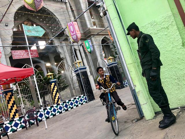 A boy rides a bicycle while looking at an army soldier stationed in front of a Sufi mosque in Kattankudy, Sri Lanka, June 11, 2019. REUTERS/Alexandra Ulmer