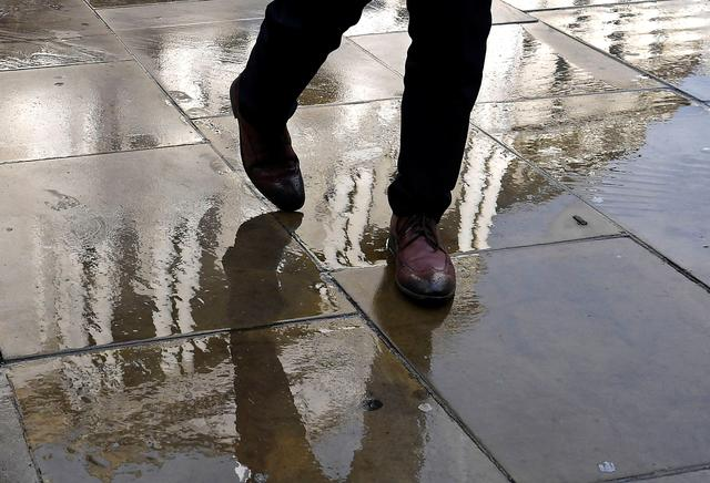 A worker walks over paving stones with the Bank of England seen reflected in them, in the City of London, Britain November 9, 2018. REUTERS/Toby Melville