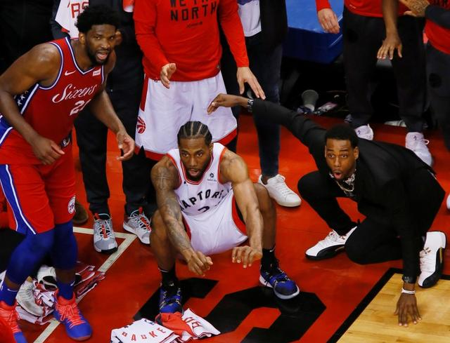 May 12, 2019; Toronto, Ontario, CAN; Philadelphia 76ers center Joel Embiid (21) and Toronto Raptors forward Kawhi Leonard (2) wait for the game winning basket by Leonard to drop in during game seven of the second round of the 2019 NBA Playoffs at Scotiabank Arena. Toronto defeated Philadelphia. Mandatory Credit: John E. Sokolowski-USA TODAY Sports