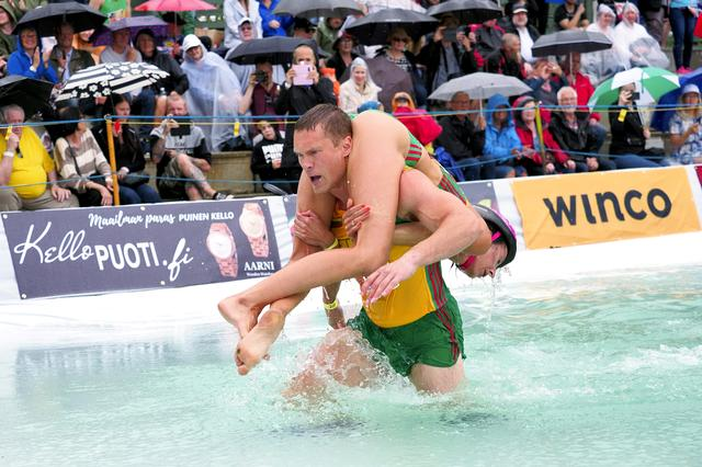 Vytautas Kirkliauskas of Lithuania carries his wife Neringa Kirkliauskiene as they compete during the Wife Carrying World Championships in Sonkajarvi, Finland, July 6, 2019. Lehtikuva / Timo Hartikainen via REUTERS