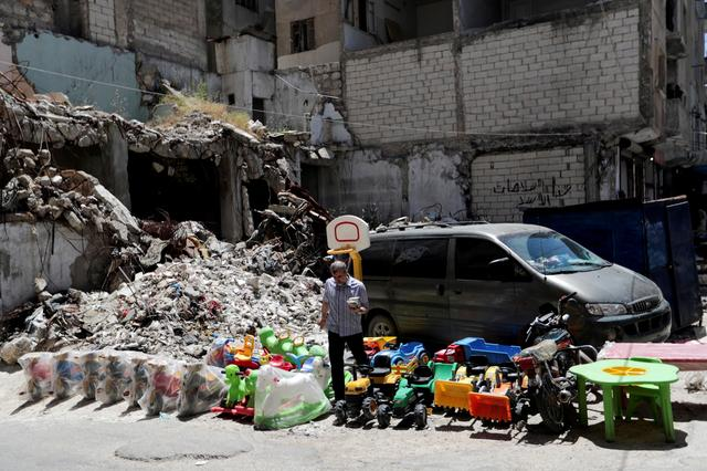 FILE PHOTO: A street vendor sells toys next to rubble of damaged buildings in the city of Idlib, Syria May 25, 2019. REUTERS/Khalil Ashawi/File Photo