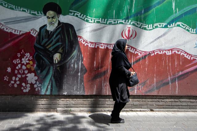 An Iranian woman walks in front of a mural of Iran's late leader Ayatollah Ruhollah Khomeini in Tehran, Iran July 7, 2019. Nazanin Tabatabaee/WANA (West Asia News Agency) via REUTERS