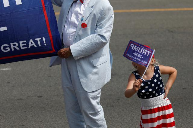 A child holds up a Trump 2020 election campaign flag at Independence Day celebrations in Washington, D.C., U.S., July 4, 2019. REUTERS/Tom Brenner