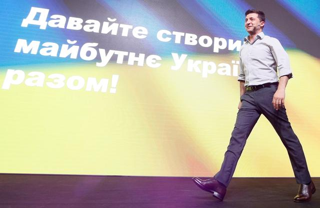 FILE PHOTO: Ukraine's President Volodymyr Zelenskiy walks on the stage at an IT conference in Kiev, Ukraine May 23, 2019. The sign on a screen reads Let's create the future of Ukraine together! REUTERS/Valentyn Ogirenko/File Photo