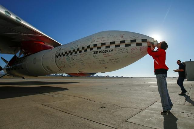 Virgin Orbit's chief engineer Kevin Sagis kisses the tip of a test rocket underneath the wing of a modified Boeing 747 jetliner prior to its takeoff and drop test of its high-altitude launch system for satellites from Mojave, California, U.S. July 10, 2019.       REUTERS/Mike Blake