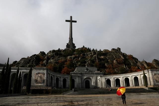 FILE PHOTO: A woman holds an umbrella at the Valle de los Caidos (The Valley of the Fallen), the mausoleum holding the remains of former Spanish dictator Francisco Franco, on the 43rd anniversary of his death in San Lorenzo de El Escorial, outside Madrid, Spain, November 20, 2018. REUTERS/Susana Vera