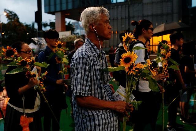 Pro-democracy activists hold sunflowers to attend a public memorial for anti-extradition bill protester Marco Leung, who died after falling from a scaffolding at the Pacific Place complex while protesting, in Hong Kong, China July 11, 2019. REUTERS/Tyrone Siu