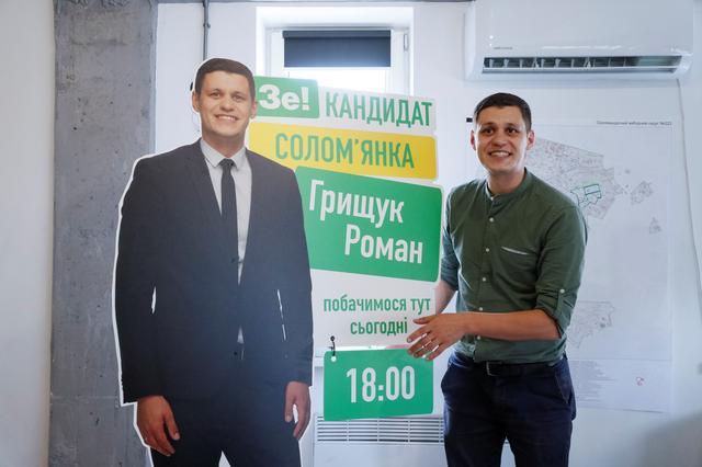Roman Hryshchuk, a 29-year-old comedian and parliamentary election candidate, shows a banner with a life-size cutout of himself at his election headquarters in Kiev, Ukraine July 4, 2019.  REUTERS/Valentyn Ogirenko