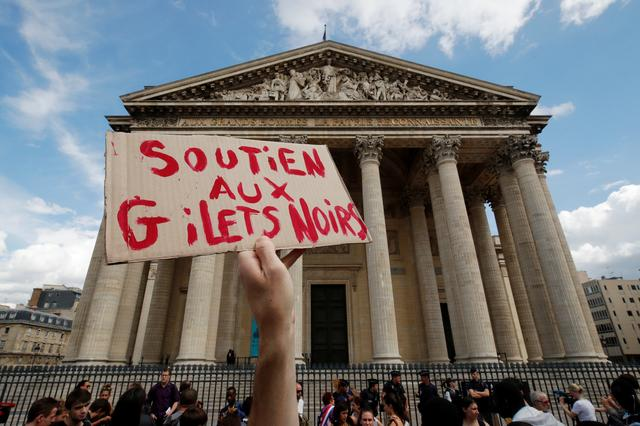 A man holds a placard which reads Support to the Gilets Noirs movement as he stands in front of the Pantheon occupied by undocumented migrants in Paris, France, July 12, 2019.  REUTERS/Philippe Wojazer