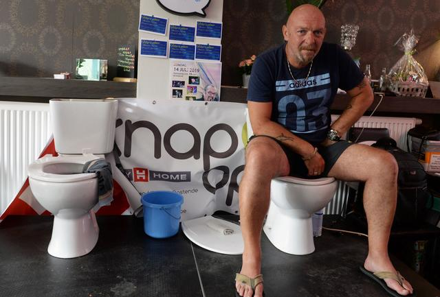 Belgian Jimmy de Frenne sits on a toilet in a cafe in an attempt to enter the Guinness Book of Records for a new record for sitting on a toilet for the longest time, in Ostend, Belgium, July 11, 2019. REUTERS/Johanna Geron
