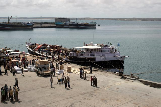 FILE PHOTO: Workers stand at the sea port of the coastal town of Kismayu in southern Somalia November 12, 2013. REUTERS/Siegfried Modola/File Photo