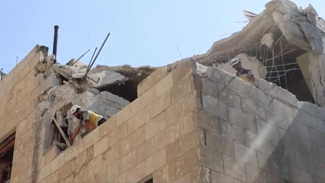 White Helmets stand on partially destroyed building after air strikes hit residential buildings in northwest Syria, in this picture grab taken from a video, July 12, 2019. White Helmets via REUTERS