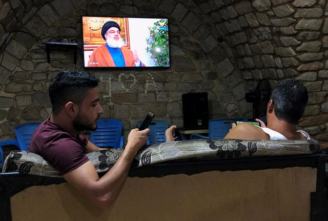 Men hold their phones as they watch Lebanon's Hezbollah leader Sayyed Hassan Nasrallah speak on television inside a coffee shop in the port city of Sidon, Lebanon July 12, 2019. REUTERS/Ali Hashisho