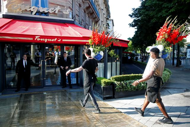 Employees bring flowers to the Fouquet's restaurant on the eve of its reopening on the Champs Elysees, almost 4 months after it was ranksacked by a yellow vests protest in Paris, France, July 13, 2019. REUTERS/Charles Platiau