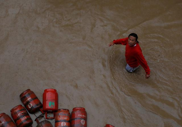 A man walks past gas cylinders in a flooded colony in Kathmandu, Nepal July 12, 2019. REUTERS/Navesh Chitrakar