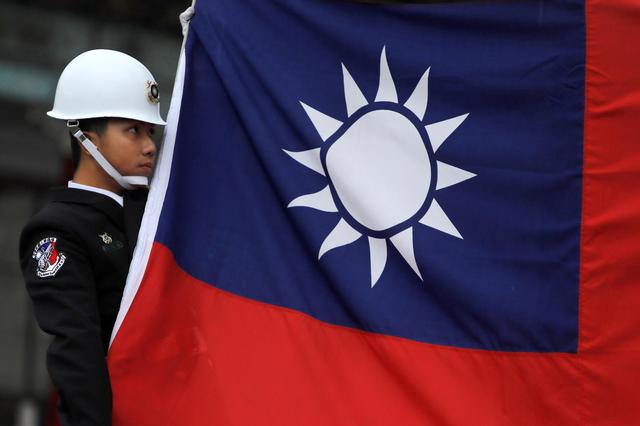 FILE PHOTO: A military honour guard holds a Taiwanese national flag as he attending flag-raising ceremony at Chiang Kai-shek Memorial Hall, in Taipei, Taiwan March 16, 2018. REUTERS/Tyrone Siu/File Photo