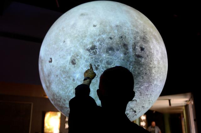 University of Colorado Boulder director of NASA/NLSI Lunar University Network for Astrophysics Research Jack Burns points out locations on a lunar globe at the Fiske Planetarium in Boulder, Colorado, U.S., June 24, 2019. REUTERS/Michael Ciaglo
