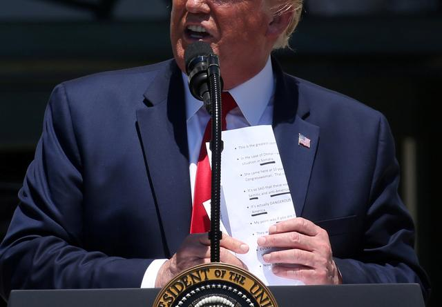 "President Donald Trump puts away talking points about four first-term Democratic congresswomen while answering questions from the media during the ""3rd Annual Made in America Product Showcase"" on the South Lawn of the White House in Washington, U.S., July 15, 2019. REUTERS/Leah Millis"