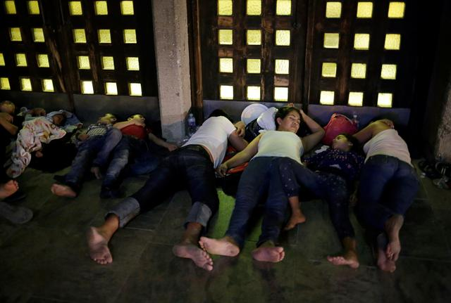 FILE PHOTO: Central American migrants, who returned to Mexico from the United States to await their court hearing for asylum seekers, as part of the legal proceedings under a new policy established by the U.S. government, sleep outside the Our Lady of Guadalupe Cathedral in Ciudad Juarez, Mexico, July 14, 2019. Picture taken July 14, 2019. REUTERS/Jose Luis Gonzalez