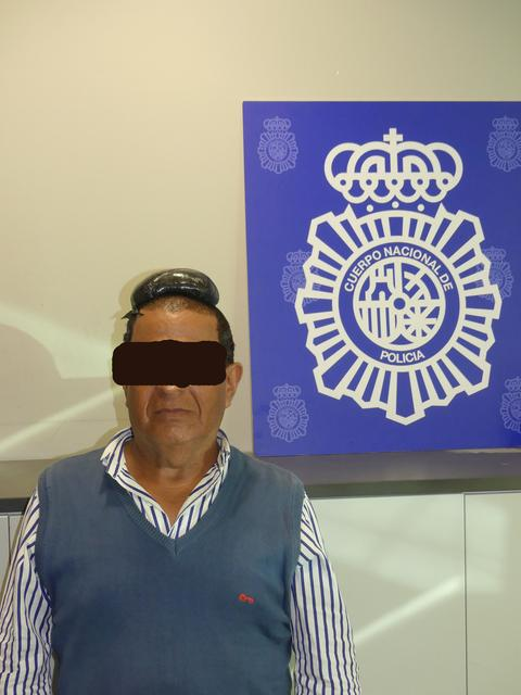 A man poses with a drug package on his head, that he hid under a toupee, after being arrested in Barcelona, Spain, in this picture released on July 16, 2019. Spanish National Police via REUTERS