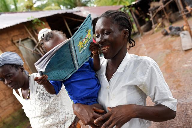 Mariatu Sesay, 15, smiles as she carries her daughter Nadia while she walks outside her house in the countryside village of Sierra Leone  July 11, 2019. REUTERS/Cooper Inveen
