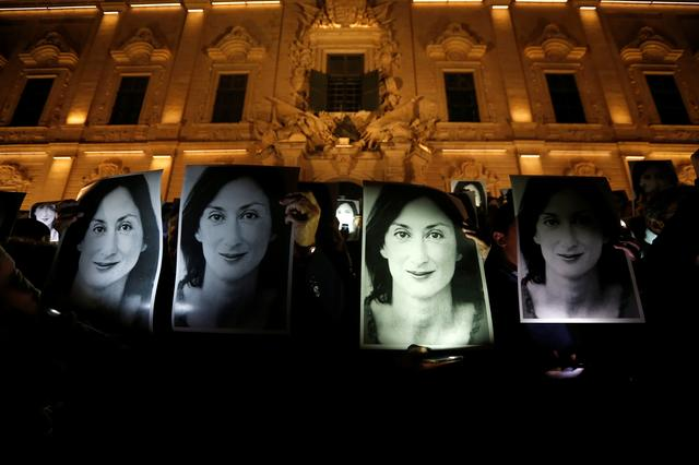 FILE PHOTO - People hold up photos of anti-corruption journalist Daphne Caruana Galizia during a protest marking eighteen months since her assassination outside the office of Prime Minister Joseph Muscat at Auberge de Castille in Valletta, Malta April 16, 2019.  REUTERS/Darrin Zammit Lupi