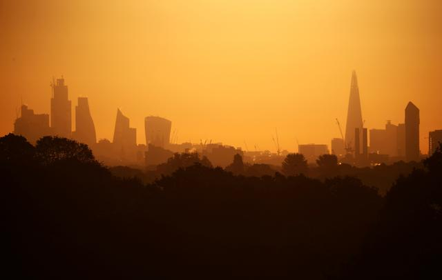 FILE PHOTO: The sun rises behind The Shard and the financial district in London, Britain, May 13, 2019. REUTERS/Hannah McKay/File Photo