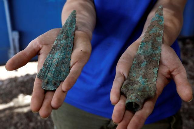 Una mujer sostiene una punta de flecha y una daga, parte los hallazgos en un gran asentamiento prehistórico descubierto por un arqueólogo israelí en Motza cerca de Jerusalén, Isareal. 16 de julio de 2019. REUTERS/Nir Elias.