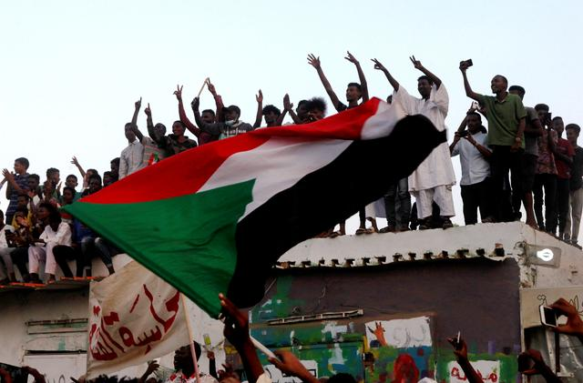 FILE PHOTO: Sudanese people chant slogans and wave their national flag as they celebrate, after Sudan's ruling military council and a coalition of opposition and protest groups reached an agreement to share power during a transition period leading to elections, along the streets of Khartoum, Sudan, July 5, 2019. REUTERS/Mohamed Nureldin Abdallah/File Photo