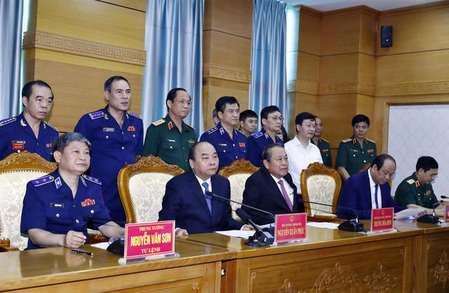 FILE PHOTO: Vietnam's Prime Minister Nguyen Xuan Phuc (2nd L, front) and Deputy Prime Minister Truong Hoa Binh (2nd R, front) speaks with sailors of Coast Guard Force on field via video call during their visit to Coast Guard Command in Hanoi, Vietnam July 11, 2019. Thong Nhat/VNA via REUTERS.
