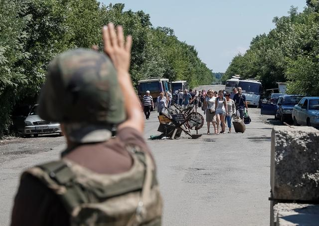 A member of the Ukrainian State Border Guard Service gives a sign to people to stop as they approach a checkpoint at the contact line between pro-Russian rebels and Ukrainian troops in Mayorsk, Ukraine July 3, 2019. REUTERS/Gleb Garanich