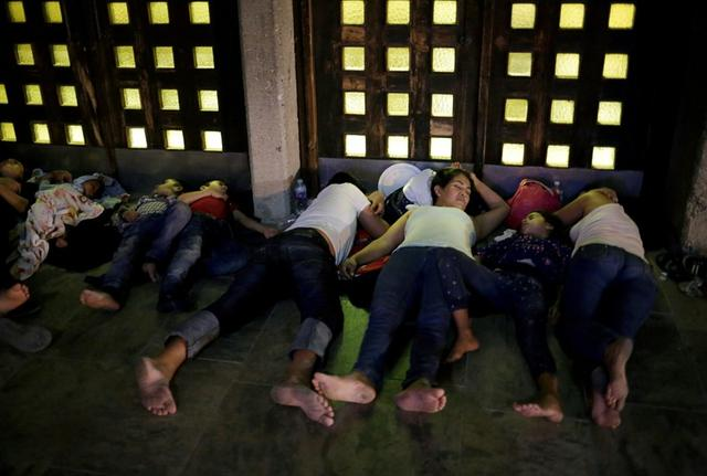FILE PHOTO: Central American migrants, who returned to Mexico from the United States to await their court hearing for asylum seekers, as part of the legal proceedings under a new policy established by the U.S. government, sleep outside the Our Lady of Guadalupe Cathedral in Ciudad Juarez, Mexico, July 14, 2019. REUTERS/Jose Luis Gonzalez/File Photo