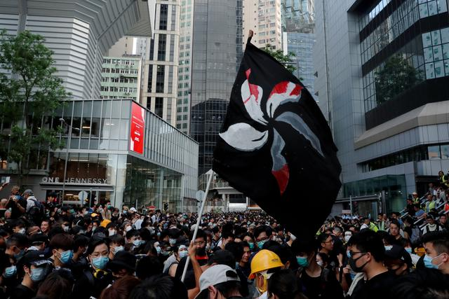 FILE PHOTO: People hold up a black flag during a protest outside police headquarters to demand Hong Kong's leaders step down and withdraw an extradition bill, in Hong Kong, China June 21, 2019. REUTERS/Tyrone Siu/File Photo