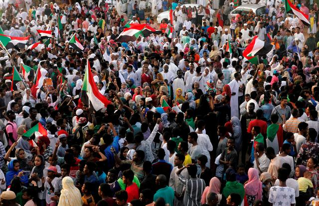 FILE PHOTO: Sudanese people celebrate in the capital Khartoum after the ruling military council and a coalition of opposition and protest groups reached agreement to share power during a transition period leading to elections, July 5, 2019. REUTERS/Mohamed Nureldin Abdallah