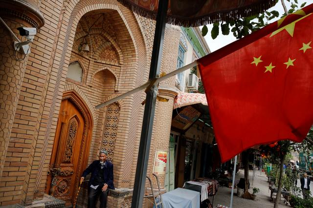 An elderly man is seen behind a Chinese national flag in the Old City in Kashgar in Xinjiang Uighur Autonomous Region, China September 6, 2018. Picture taken September 6, 2018.   REUTERS/Thomas Peter
