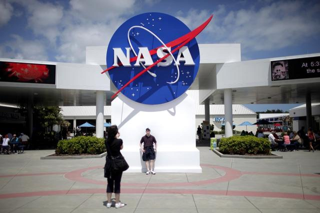 FILE PHOTO: Tourists take pictures of a NASA sign at the Kennedy Space Center visitors complex in Cape Canaveral, Florida April 14, 2010. REUTERS/Carlos Barria/File Photo