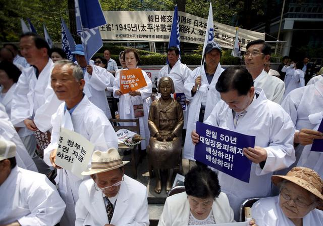 FILE PHOTO: Descendants of Koreans who were conscripted to the Japanese imperial army or recruited for forced labor under Japan's colonisation surround a statue of a girl as they attend an anti-Japan rally in front of the Japanese embassy in Seoul, South Korea, June 22, 2015.   REUTERS/Kim Hong-Ji/File Photo