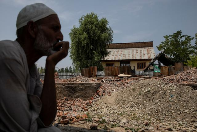 Abdul Hamid Mir, uncle of Atif Mir, 12, who was taken hostage by militants and later killed in crossfire with Indian troops, sits next to his destroyed house, in Bandipore, north of Srinagar, July 10, 2019. REUTERS/Danish Siddiqui