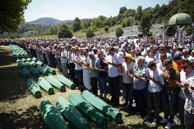 FILE PHOTO: People pray near coffins of their relatives, who are newly identified victims of the 1995 Srebrenica massacre, which are lined up for a joint burial in Potocari near Srebrenica, Bosnia and Herzegovina, July 11, 2017. REUTERS/Dado Ruvic/File Photo