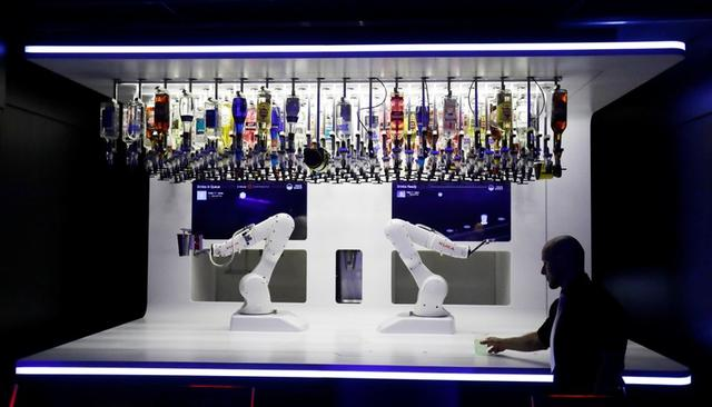 A waiter takes a drink prepared by a robotic bartender in Karlovy Lazne Music Club in Prague, Czech Republic, July 17, 2019. REUTERS/David W Cerny