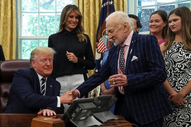 U.S. President Donald Trump greets Apollo 11 Lunar Module Pilot Buzz Aldrin as first lady Melania Trump and guests look on during an Apollo 11 50th anniversary commemoration event in the Oval Office of the White House in Washington, U.S., July 19, 2019. REUTERS/Leah Millis