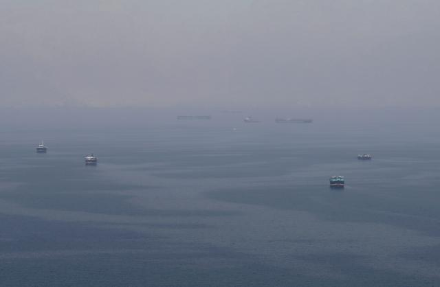 FILE PHOTO: Traditional Omani boats known as dhows, and cargo ships are seen sailing towards the Strait of Hormuz, off the coast of Musandam province, Oman, July 21, 2018.  REUTERS/Hamad I Mohammed/File Photo