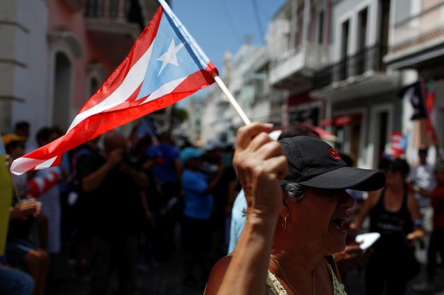 A woman shouts as she waves a Puerto Rican flag during the seventh day of protest calling for the resignation of Governor Ricardo Rossello in San Juan, Puerto Rico July 19, 2019. REUTERS/Marco Bello