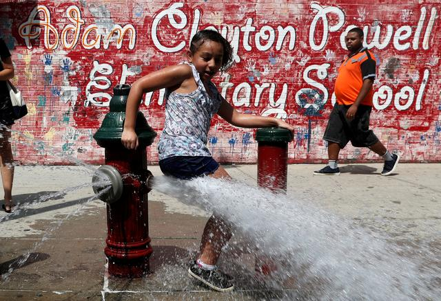A girl cools off from the heat in water from an open fire hydrant in the Washington Heights section of upper Manhattan in New York City, New York, U.S., July 19, 2019. REUTERS/Mike Segar
