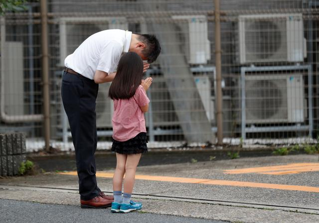People pray for victims of the torched Kyoto Animation building in Kyoto, Japan, July 20, 2019. REUTERS/Kim Kyung-Hoon