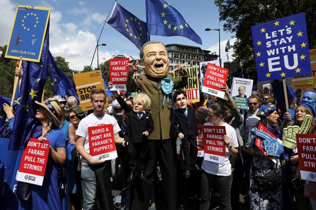 A person dressed as Brexit Party Leader Nigel Farage holds puppets of Boris Johnson and Jeremy Hunt during the anti-Brexit 'No to Boris, Yes to Europe' march in London, Britain, July 20, 2019   REUTERS/Kevin Coombs