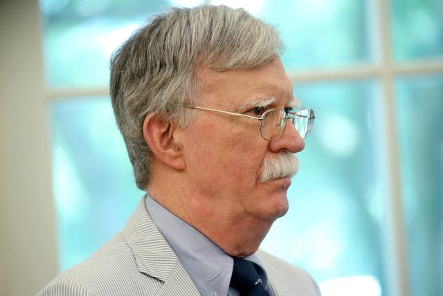 FILE PHOTO: U.S. national security adviser John Bolton looks on as U.S. President Donald Trump and first lady Melania Trump acknowledge former astronauts and their family members during an Apollo 11 moon landing 50th anniversary commemoration in the Oval Office of the White House in Washington, U.S., July 19, 2019. REUTERS/Leah Millis