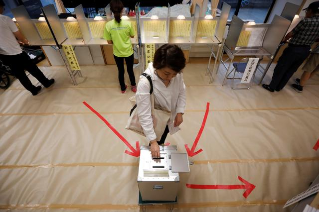 A voter casts a ballot at a voting station during Japan's upper house election in Tokyo, Japan July 21, 2019. REUTERS/Issei Kato